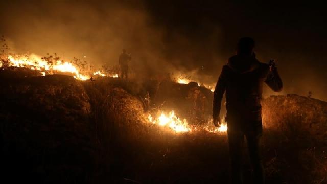 A man uses his phone near a fire in Houla village near the Lebanese-Israeli border, in southern Lebanon