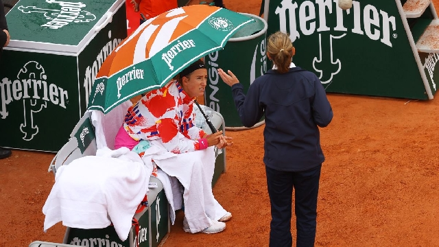 Victoria Azarenka talks with a match supervisor during a pause in her first-round match at the 2020 French Open.