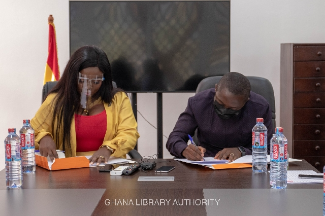 Stacy Amoateng (left) signing the MoU with a representative of the Ghana Library Authority