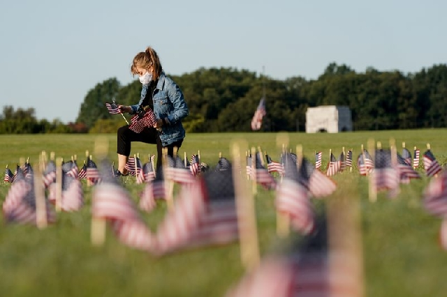 A volunteer places American flags representing some of the 200,000 lives lost in the United States in the coronavirus disease