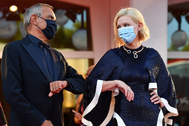 Actor and Venice Film Festival jury president Cate Blanchett touches elbows with festival director Alberto Barbera.